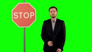 Businessman standing near a stop sign on laptop on a Green Screen, Chroma Key