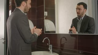 Businessman takes a look at himself in the mirror