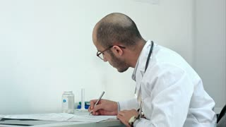 Busy male physician working with medical forms and papers in hospital office room