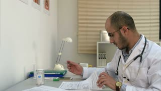 Busy male physician working with papers and having phone conversation in his office