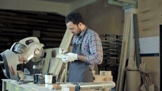 Carpenter do measurements on wood plank in carpentry workshop