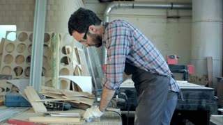 Carpenter working with electric planer and make notes in his notebook in workshop