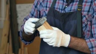 Carpenter working with wooden bar in workshop