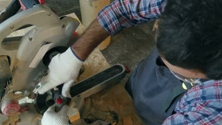 Carpenter works with wooden bar in workshop near electric saw