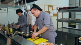 Chef and two trainees busy working in the kitchen