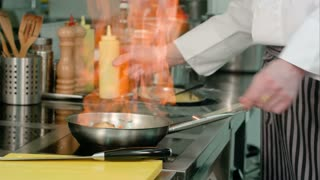Chef cooking vegetables with flame