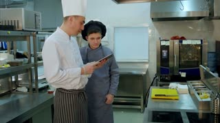 Chef explaining something to cook trainee in hat using digital tablet