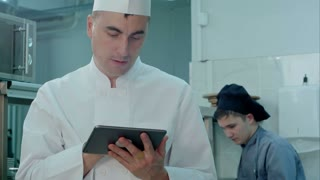 Chef looking for recipes on digital tablet in the professional kitchen