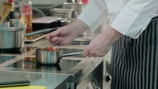 Chef male hands checking meals being cooked on the stove