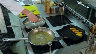 Chef putting fish in a frying pan