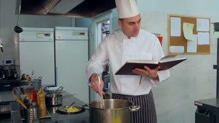 Chef reading cook book and making some dish