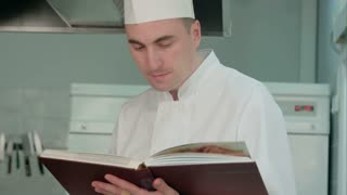 Chef reading cook book and preparing ingredients
