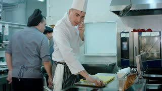 Chef talking on the phone and tossing ingredients on a frying pan in the restaurant kitchen