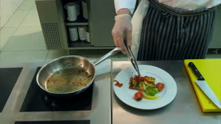 Chef's hand putting fried vegetables on a plate