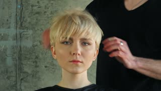 Closeup on young woman getting new hairdress by hairdresser