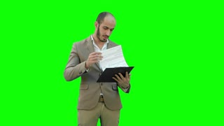Concentrated businessman reading financial report on a Green Screen, Chroma Key