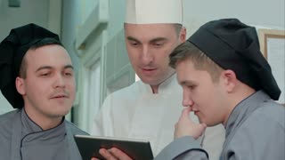 Concentrated chef showing his trainees something on digital tablet