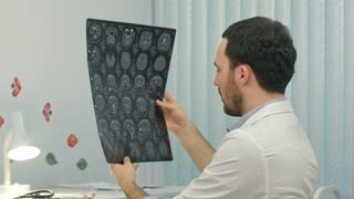 Concentrated male doctor looking at x-ray picture in the medical office
