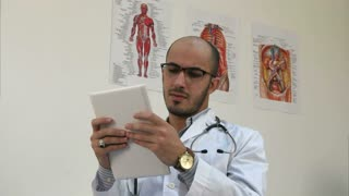 Concentrated male medical worker using digital tablet