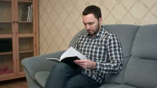Concentrated young man reading book sitting on the sofa