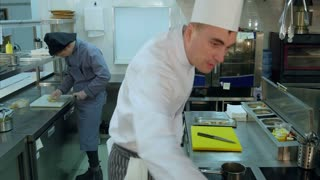 Cook trainee slicing lemon while chef spicing shrimps