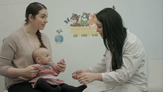 Cute baby being examine by pediatrician with toy