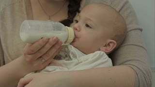 Cute baby eating milk from bottle