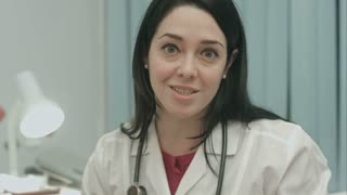 Cute female doctor smiling and says good news to patient