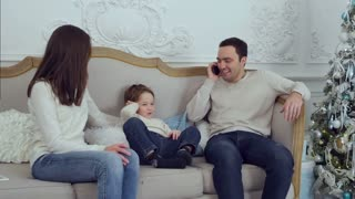 Cute little boy sitting on the sofa immitating his father talking on the phone
