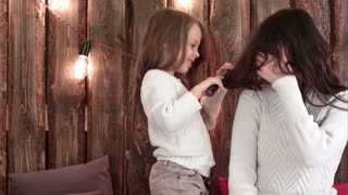 Cute little daughter combing dark haired mother sitting on a sofa
