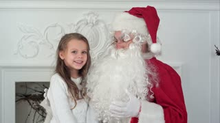 Cute little girl singing a Christmas song sitting on Santa Claus lap