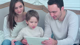 Dad, mom and their young son having fun by playing together with a tablet sitting on a couch