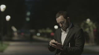 Displeased bearded businessman use smart phone, while standing in the city street,business man reading messages,  brunette using cell phone at evening outdoors, park