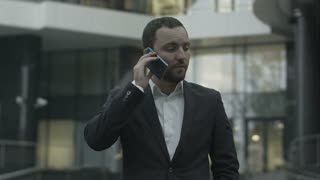 Displeased business man seriously talking by phone, standing outside the office