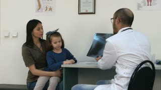 Doctor explaining chest xray image to mother holding little daughter in her arms