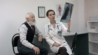 Doctor explaining x-ray results to senior patient.