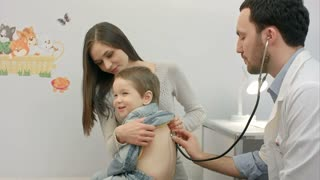 Doctor is examining boy with a stethoscope