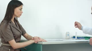Doctor prescribing pills to female patient and explaining side effects