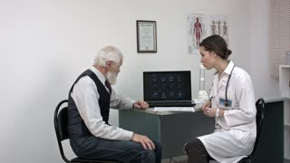 Doctor showing elderly patient's mri results on laptop.