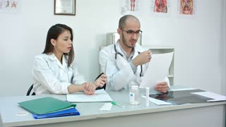 Doctor showing his female trainee how to read cardiogram while she making notes