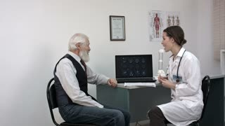 Doctor showing mri on laptop and telling good news to senior patient.