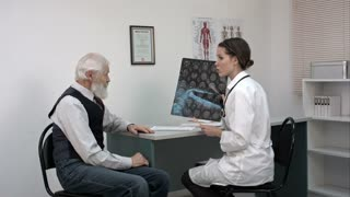 Doctor showing mri to the old patient and explaining something.