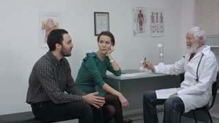 Doctor talking nicely to couple in hospital.