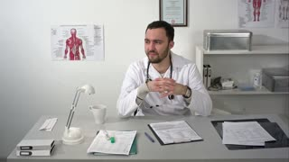 Doctor talking to camera, smiling and showing thumbs up