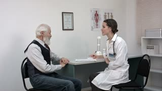 Doctor talking to senior man at her office.