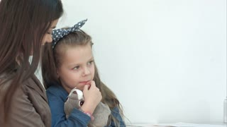 Doctor trying to cheer up little girl patient hugging her bunny toy