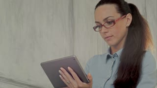 Elegant businesswoman using tablet PC in a bright office