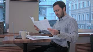 exhausted businessman in a coffee shop searching in documents