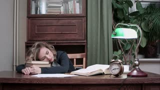 Exhausted female fallen asleep on the stack of books at her desk and woken up by an alarm quickly takes her books and papers, drinks coffee and leaves