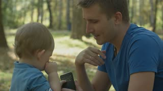 Father helps crying son to use cell phone in park